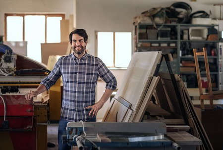 Woodworker smiling while standing by equipment in his workshop