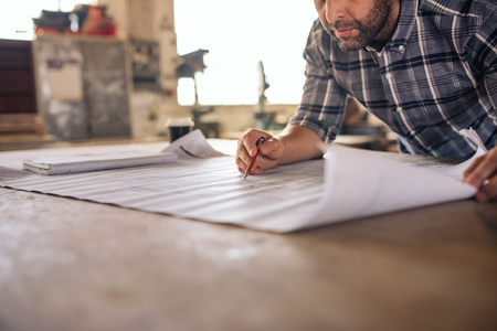 Woodworker leaning over a bench reading furniture design blueprints