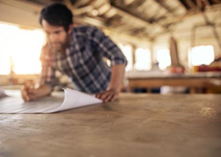Craftsman leaning on a workshop bench reading furniture plans