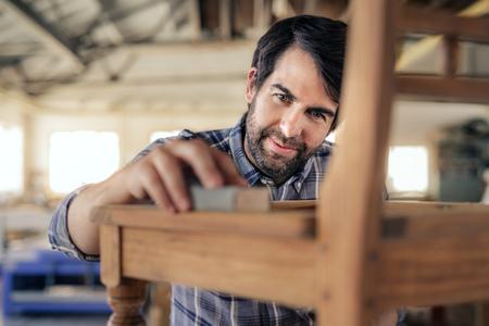 Fabricant de meubles souriant ponçant une chaise dans son atelier