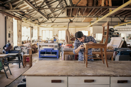 Furniture maker sanding a chair on his workshop table Stock Photo