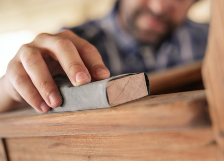 Hands of furniture maker sanding a chair in his workshop Stock Photo