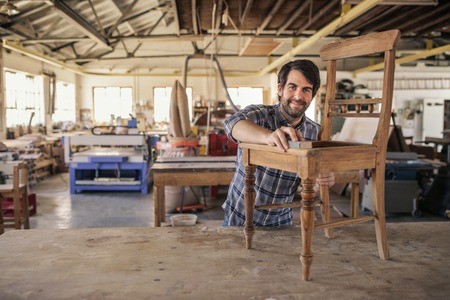 Smiling furniture maker sanding a chair in his woodworking shop