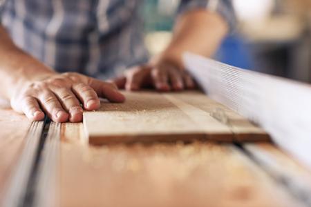 Schrijnwerker zaagt planken van hout in zijn timmerwerkplaats