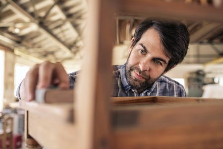 Woodworker sanding a chair in his furniture making workshop