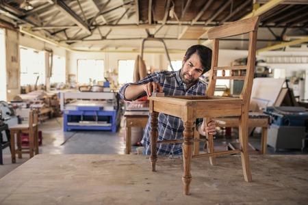 Furniture maker sanding a chair on workshop bench