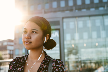 Content Asian businesswoman listening to music at a bus stop Imagens