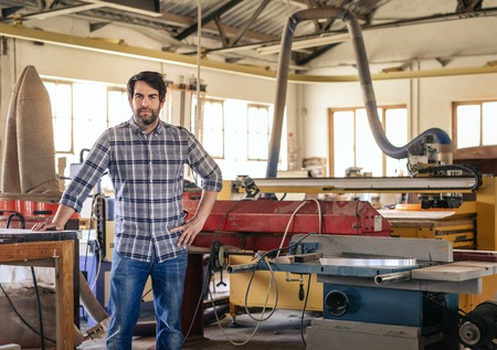Young entrepreneur leaning on a table in his large workshop