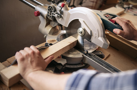 Woodworker cutting wood with a saw in his carpentry workshop Stock Photo