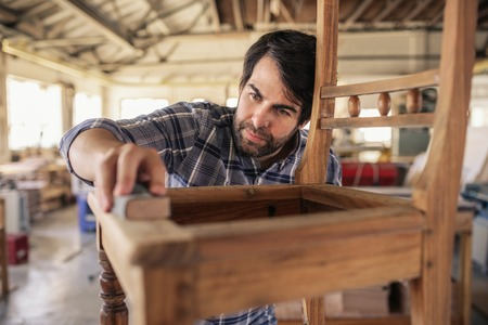 Skilled furniture maker sanding a chair in his workshop Stock Photo - 116621454