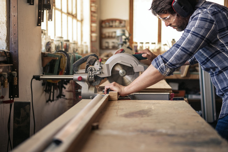 Woodworker cutting wood with a mitre saw in his workshop