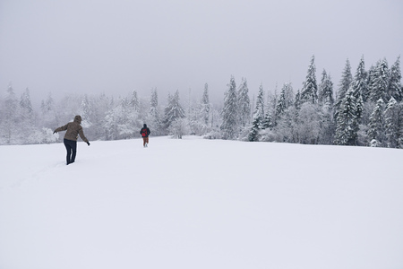 Couple hiking through a snow covered forest clearing