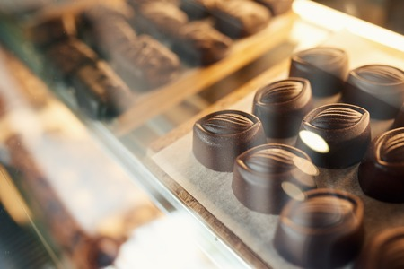 Pieces of chocolate sitting in a confectionary shop display case Banque d'images - 116621554
