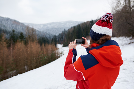 Young woman taking pictures while out for a winter hike