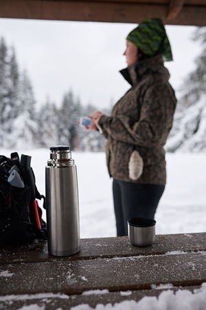 Young woman warming up with coffee during a winter hike