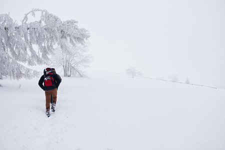 Couple hiking along a snowy trail in the wintertime Stockfoto