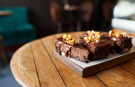 Four slices of chocolate cake sitting on a bakery table Banque d'images