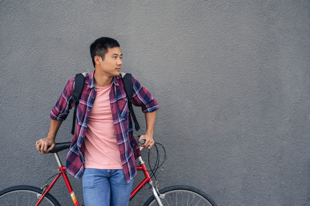 Young man leaning with his bike against a gray wall