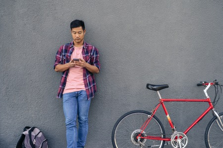 Young man sending a text while standing with his bike