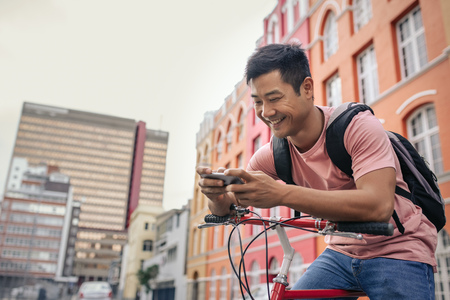 Smiling young man sitting on his bike sending a text Stock fotó