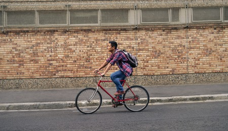 Young Asian man riding his bicycle down a city street