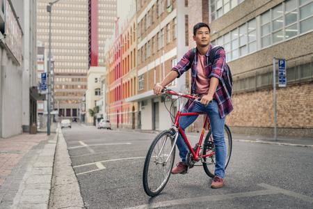 Junger Mann sitzt auf seinem Fahrrad auf einer Stadtstraße Standard-Bild