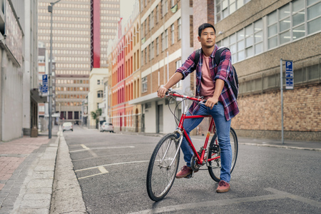 Young man sitting on his bicycle on a city street