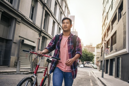 Young man walking with his bike down a city street