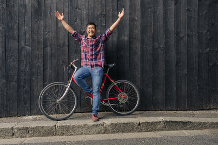 Smiling young man with a bike raising his arms skyward 版權商用圖片