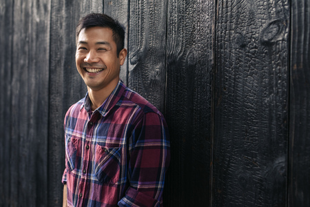 Young Asian man laughing while leaning against a dark wall