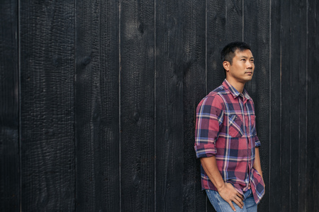 Confident young Asian man leaning against a dark wall outside 스톡 콘텐츠