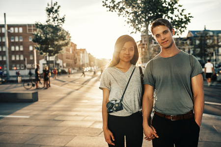 Smiling couple holding hands while standing together in the city