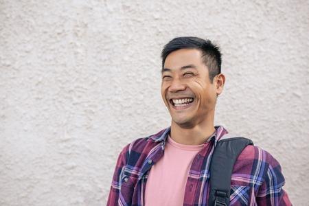 Joven asiático de pie en una calle de la ciudad riendo Foto de archivo