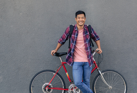 Cool smiling man standing with his bike against a wall