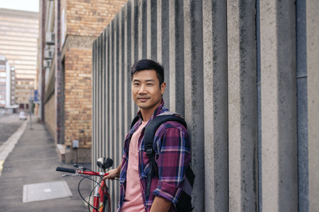 Smiling young man leaning against a wall with his bike