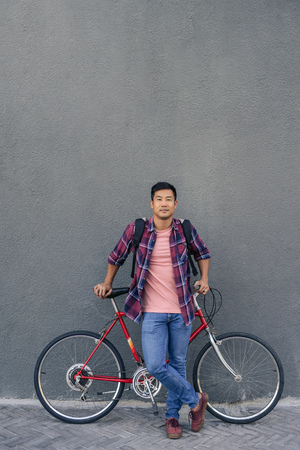 Young man standing with his bike against a gray wall Imagens