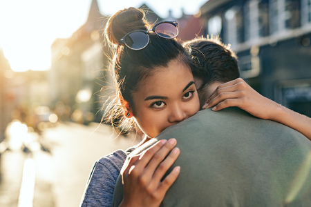 Young woman hugging her boyfriend on a city street 版權商用圖片