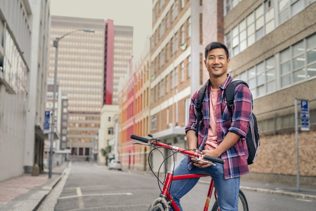 Smiling young man sitting on his bike in the city
