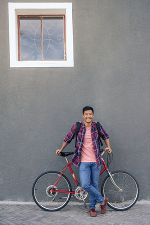 Smiling young man standing with his bike against a wall Imagens