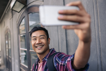 Young Asian man smiling while taking selfies outside