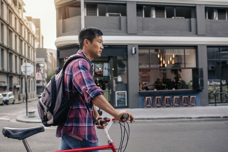Young Asian man walking with his bike in the city
