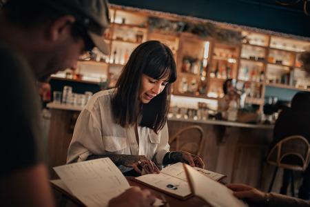 Friends reading drinks menus in a bar at night