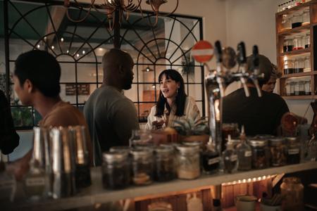 Diverse Freunde unterhalten sich nachts in einer Bar bei einem Drink Standard-Bild