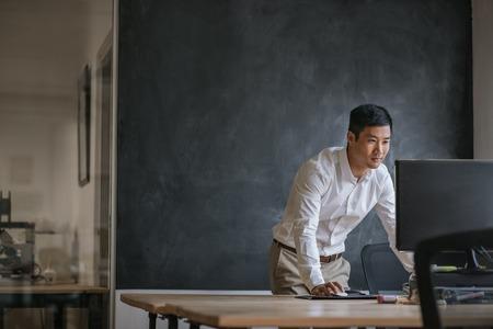 Asiatischer Geschäftsmann, der an seinem Computer in einem Büro arbeitet