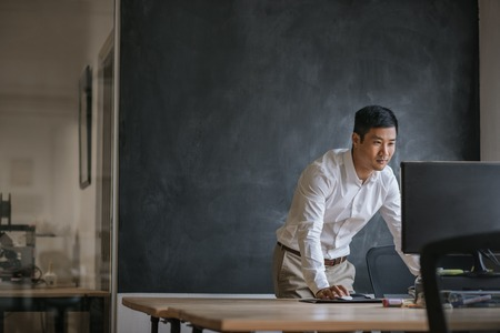 Empresario asiático trabajando en su computadora en una oficina.