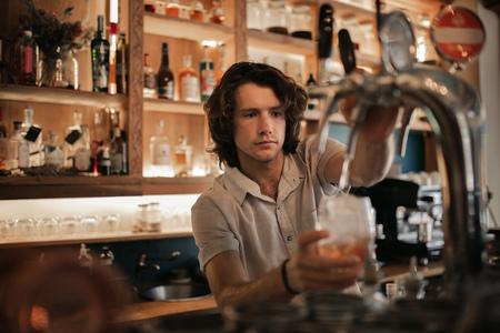 Bartender preparing drinks behind a bar counter at night Imagens