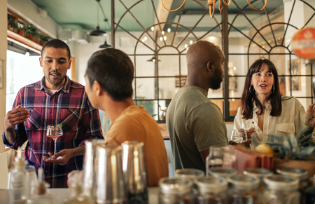 Diverse young friends having drinks together in a bar