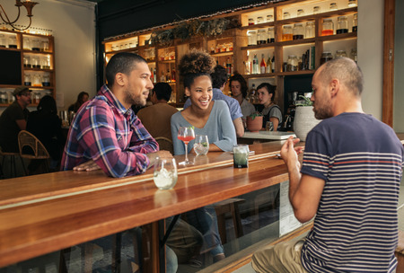 Smiling friends talking over drinks in a trendy bar