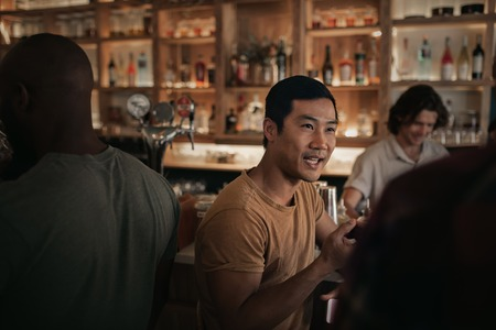 Young man talking with friends in a busy bar