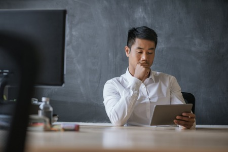 Asian businessman sitting at his desk working on a tablet